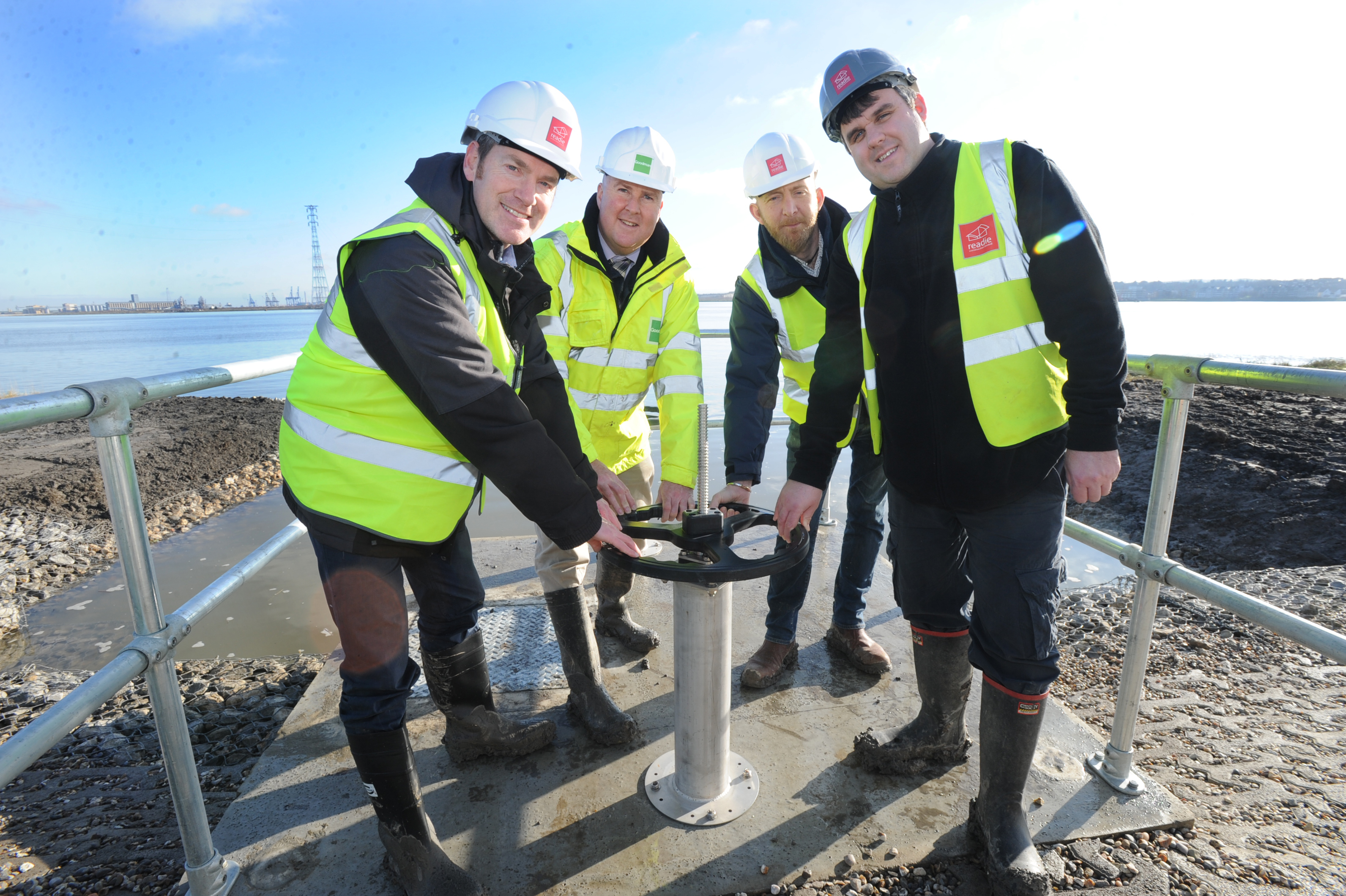Environmental officers opening the inlet valve to allow the river Thames water into the Oliver Road Lagoons development in Essex