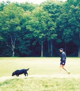 A jogger runs to maintain his health with his dog at a Land Trust site