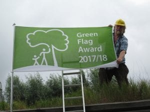 Ranger Tony Day raises the Green Flag at Greenwich Peninsula Ecology Park