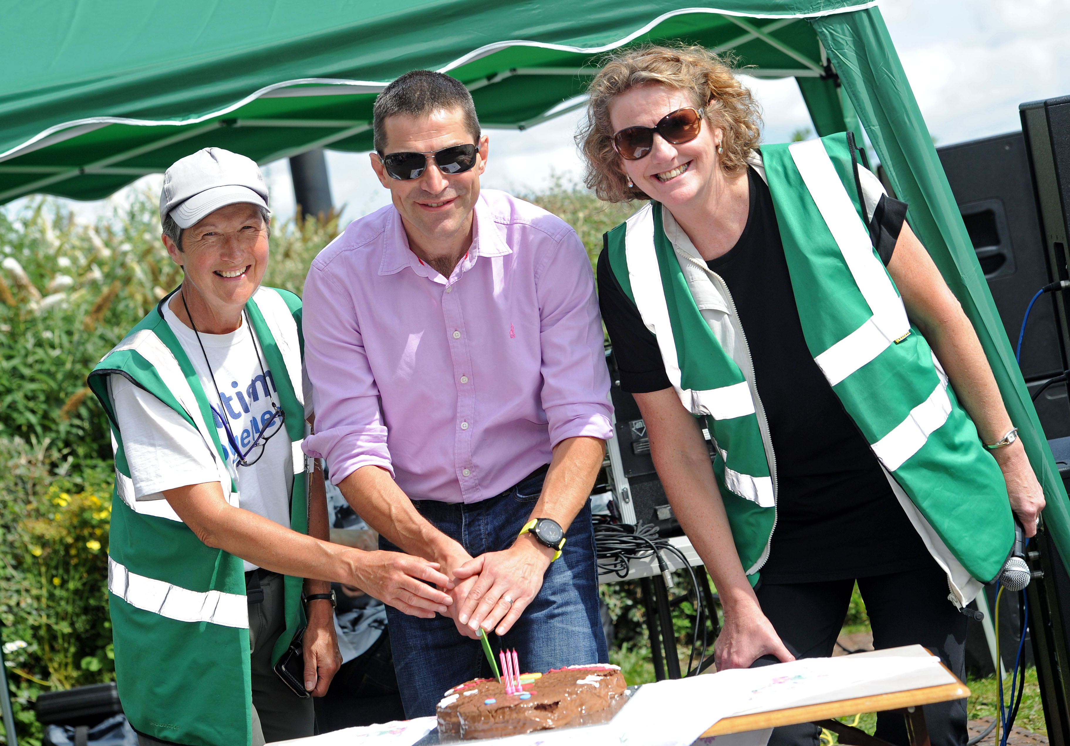 Park ranger Anne Litherland, Autism Together CEO Robin Bush and Alison Kelly from the Friends of Port Sunlight River Park cut a cake to celebrate the park's third birthday.